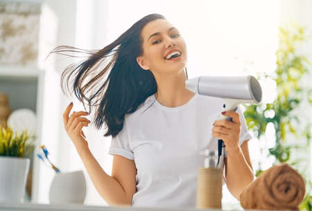 Happy young woman is blowing dry hair in the bathroom. Banque d'images - 117287541