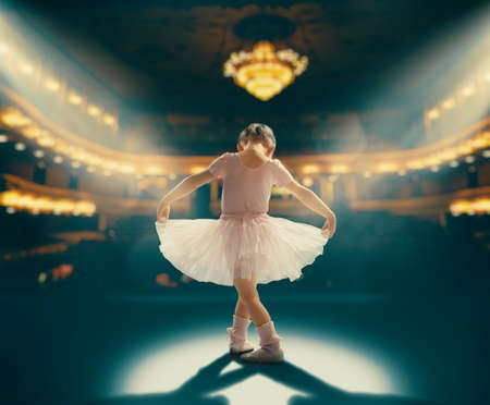 Cute little girl dreaming of becoming a ballerina. Child girl in a pink tutu dancing on the stage. Baby girl is studying ballet. Stock Photo