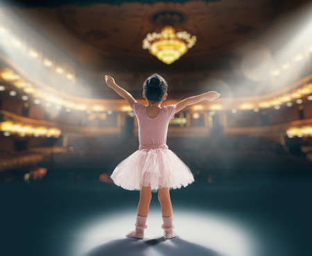 Cute little girl dreaming of becoming a ballerina. Child girl in a pink tutu dancing on the stage. Baby girl is studying ballet. Фото со стока