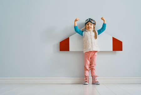 Een klein kindmeisje in een astronautenkostuum speelt en droomt ervan een ruimtevaarder te worden. Portret van grappige jongen op een achtergrond van grijze muur.