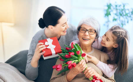 Happy womens day! Child daughter is congratulating mom and granny giving them flowers tulips. Grandma, mum and girl smiling and hugging. Family holiday and togetherness.