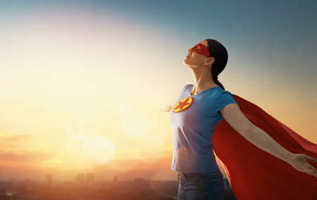 Joyful beautiful young woman in superhero costume posing on sunset background. 스톡 콘텐츠