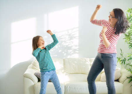 Happy loving family. Mother and her daughter child girl playing and dancing together 版權商用圖片