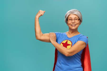 Joyeuse belle femme senior en costume de super-héros posant sur fond turquoise.