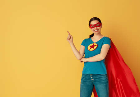 Joyful beautiful young woman in superhero costume posing on yellow background.