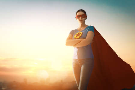 Joyful beautiful young woman in superhero costume posing on sunset background. Stock fotó