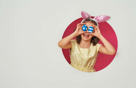 Cute little child wearing bunny ears on Easter day. Girl with painted eggs on white and pink background. Standard-Bild - 118459244