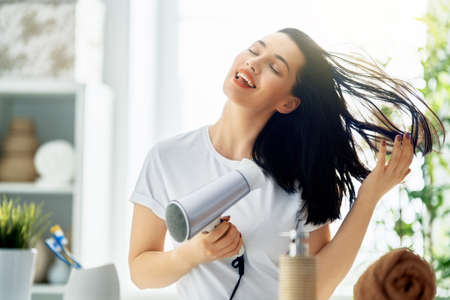 Happy young woman is blowing dry hair in the bathroom.