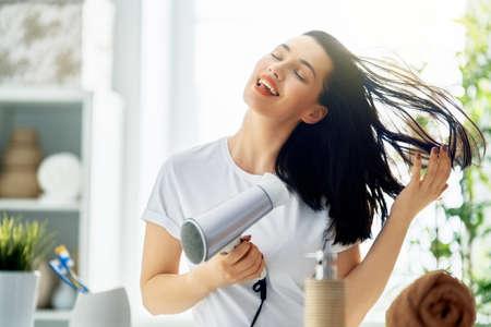 Heureuse jeune femme souffle les cheveux secs dans la salle de bain.