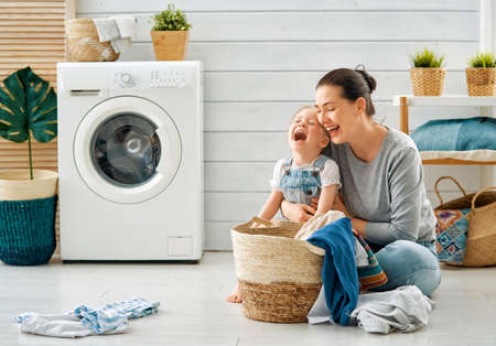 Beautiful young woman and child girl little helper are having fun and smiling while doing laundry at home. Фото со стока - 118648287