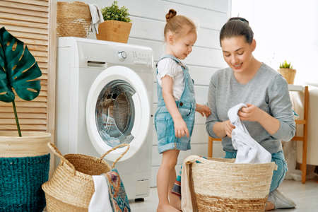 Beautiful young woman and child girl little helper are having fun and smiling while doing laundry at home. Фото со стока - 118648291