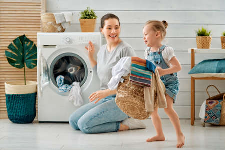 Beautiful young woman and child girl little helper are having fun and smiling while doing laundry at home. Archivio Fotografico - 118648460