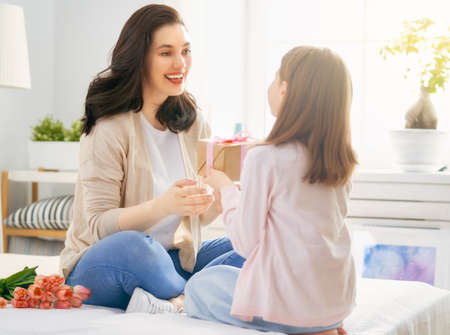 Happy womens day! Child daughter is congratulating mom and giving her flowers tulips. Mum and girl smiling. Family holiday and togetherness.