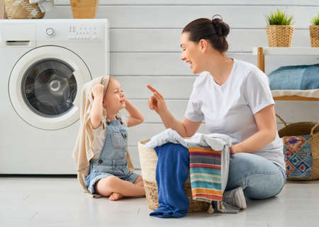 Beautiful young woman and child girl little helper are having fun and smiling while doing laundry at home. Stock Photo
