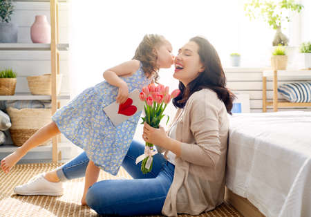 Happy mother's day! Child daughter is congratulating mom and giving her flowers tulips. Mum and girl smiling. Family holiday and togetherness.