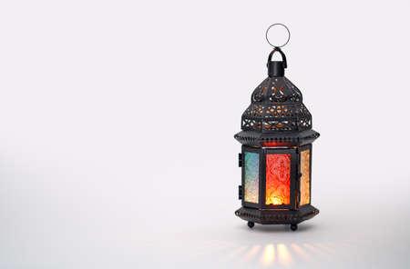 Decoratieve Arabische lantaarn met brandende kaars gloeien op witte achtergrond. Feestelijke wenskaart, uitnodiging voor islamitische heilige maand Ramadan Kareem.