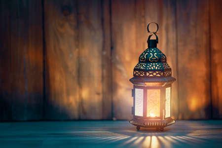 Ornamental Arabic lantern with burning candle glowing at night. Festive greeting card, invitation for Muslim holy month Ramadan Kareem. Archivio Fotografico