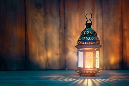 Ornamental Arabic lantern with burning candle glowing at night. Festive greeting card, invitation for Muslim holy month Ramadan Kareem. 免版税图像