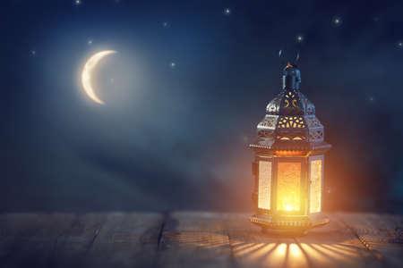 Ozdobna arabska latarnia z płonącą świecą świecącą w nocy. Świąteczna kartka z życzeniami, zaproszenie na muzułmański święty miesiąc Ramadan Kareem.