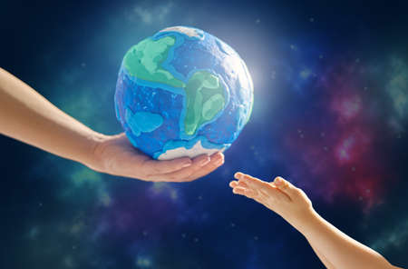Child and adult holding planet in hands against space background. Earth day holiday concept. Stock Photo