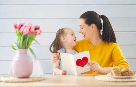 Happy mothers day! Child daughter is congratulating mom and giving her card. Mum and girl smiling. Family holiday and togetherness.