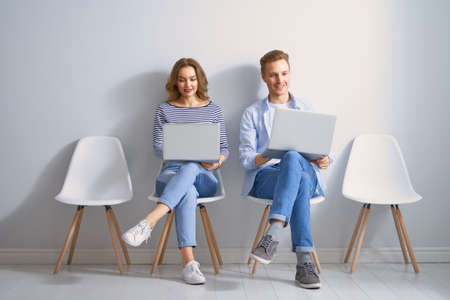 Young couple is using a laptop on white wall background Фото со стока