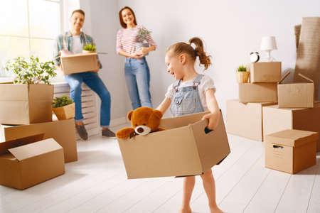 행복한 젊은 가족이 새 아파트로 이사하고 있습니다. 상자와 부모와 딸입니다.