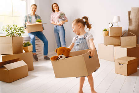 Glückliche junge Familie zieht in eine neue Wohnung. Eltern und Tochter mit Kisten.
