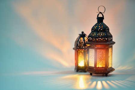 Decoratieve Arabische lantaarn met brandende kaars gloeien op witte achtergrond. Feestelijke wenskaart, uitnodiging voor islamitische heilige maand Ramadan Kareem. Stockfoto