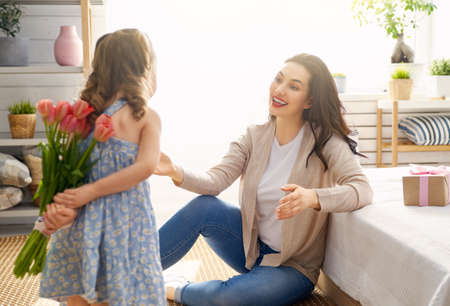 Happy mothers day! Child daughter is congratulating mom and giving her flowers tulips. Mum and girl smiling. Family holiday and togetherness.
