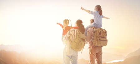 gelukkige familie bij zonsondergang. vader, moeder en twee kinderen dochters die plezier hebben en spelen in de natuur. het kind zit op de schouders van zijn vader.