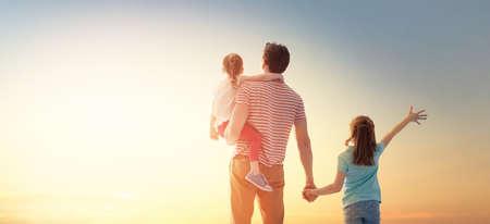 Glückliche liebende Familie. Vater und seine Töchter Kinder spielen und umarmen sich im Freien. Süße kleine Mädchen und Papa. Standard-Bild