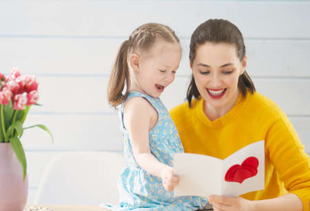 Happy mother's day! Child daughter is congratulating mom and giving her card. Mum and girl smiling. Family holiday and togetherness. 免版税图像