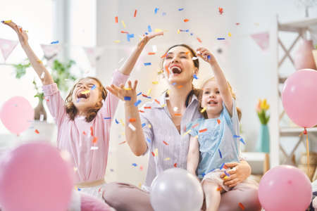 Funny time. Mom and her children daughters are playing at home. Girls are throwing confetti. Family holiday and togetherness.