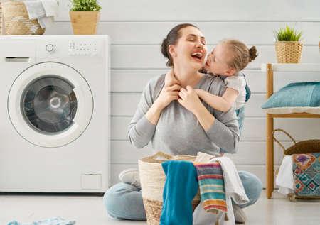Hermosa joven y niña pequeña ayudante se divierten y sonríen mientras lavan la ropa en casa. Foto de archivo