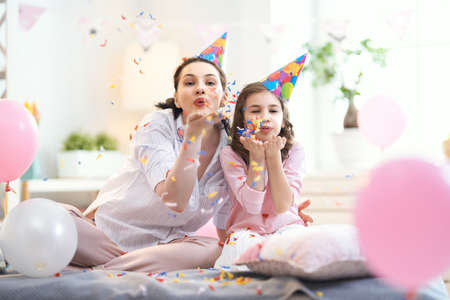 Funny time. Mom and her child daughter are playing at home. Girls are throwing confetti. Family holiday and togetherness. Stockfoto