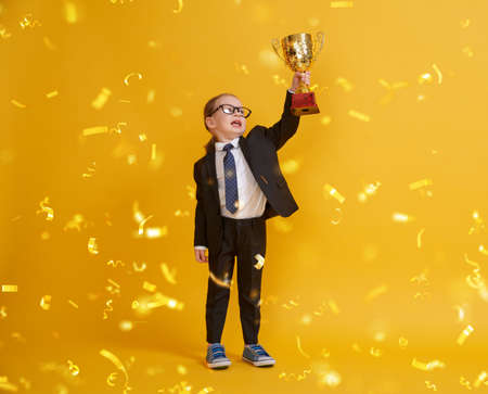 Little child is winner. Kid on the background of bright yellow wall. Smart power concept. Golden confetti and the Cup for first place. Imagens