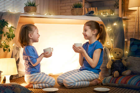 Two cute happy girls play at home. Funny lovely sisters are having fun in children room. Girls play tea-party and drink tea from cups. Stock Photo