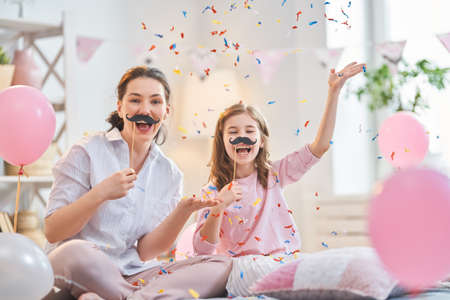 Funny time. Mom and her child daughter are playing at home. Cute girls are holding paper mustache on stick. Family holiday and togetherness.
