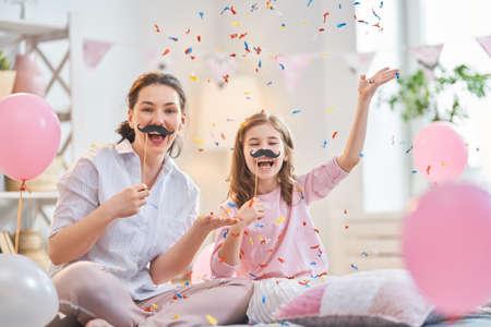 Lustige Zeit. Mama und ihre Kindertochter spielen zu Hause. Süße Mädchen halten Papierschnurrbart am Stock. Familienurlaub und Zweisamkeit.
