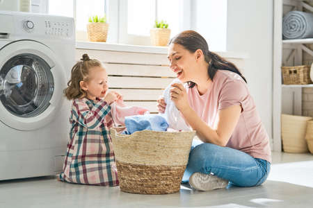 Beautiful young woman and child girl little helper are having fun and smiling while doing laundry at home. Archivio Fotografico