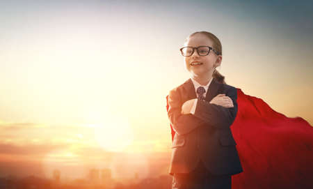 superhero businessman child on sunset background. the concept of success, leadership and victory in education.