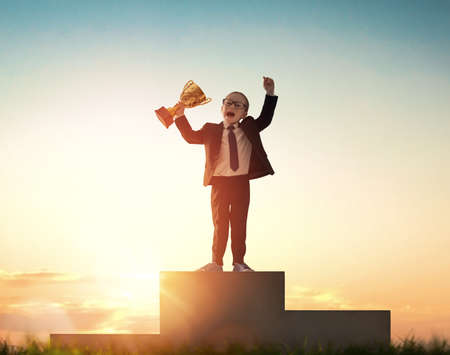 Little child is winner. Kid on sunset background. Smart power concept. The Cup for first place. Imagens