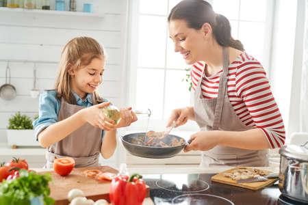 Cibo sano a casa. Famiglia felice in cucina. Madre e figlia stanno preparando un pasto adeguato.