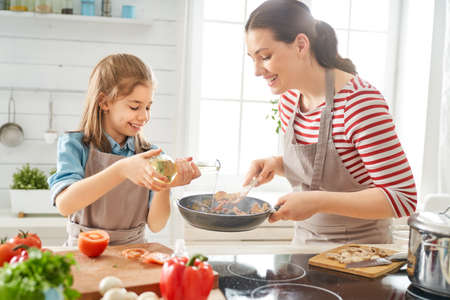 Healthy food at home. Happy family in the kitchen. Mother and child daughter are preparing proper meal. Stockfoto - 123150941