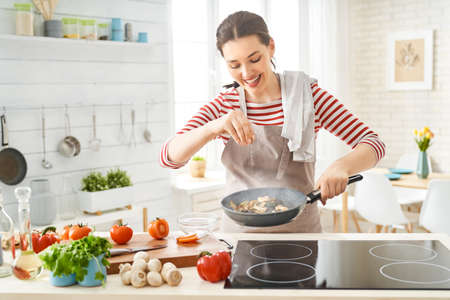 Healthy food at home. Happy woman is preparing the proper meal in the kitchen.