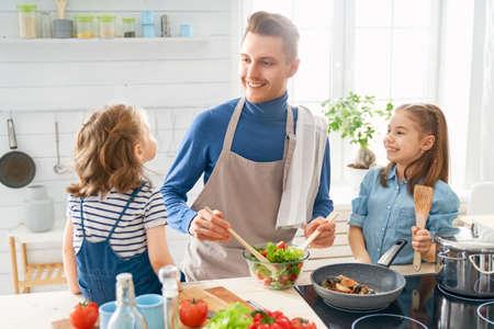 Cibo sano a casa. Famiglia felice in cucina. Le figlie del padre e dei bambini stanno preparando il pasto adeguato. Archivio Fotografico