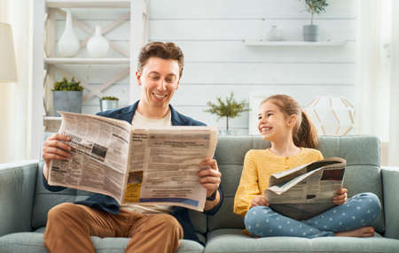 Happy loving family. Daddy and his daughter child girl are reading newspapers together. Father's day concept. Banque d'images