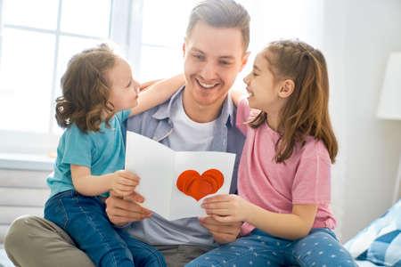 Alles gute zum Vatertag! Kindertöchter, die Papa gratulieren und ihm eine Postkarte geben. Papa und Mädchen lächeln und umarmen sich. Familienurlaub und Zweisamkeit.