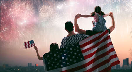 Patriotic holiday. Happy family, parents and daughter child girl with American flag outdoors. USA celebrate 4th of July. 版權商用圖片